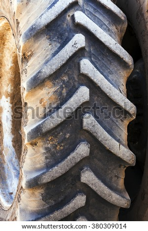 photographed close-up wheels of the tractor, drove off. dirty wheels - stock photo