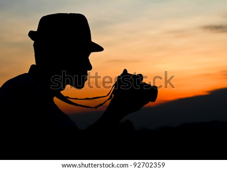 Photographer's silhouette. Photographer silhouette, staring at a camera review.