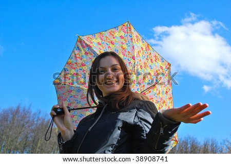 Picture of a young happy smiling girl standing under the rain with umbrella - stock photo