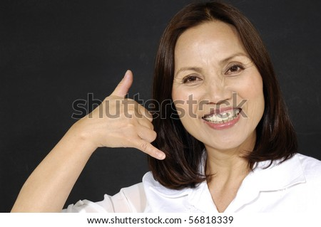 ,picture of lovely woman making a call me gesture on black - stock photo
