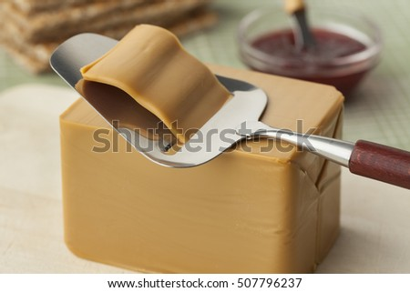 Piece of norwegian flotemysost cheese and a slicer