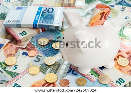 Piggy bank with ten euro  on money background - stock photo