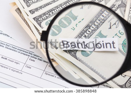 Pile of american dollars money under magnifying glass - stock photo