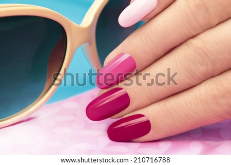 Pink manicure covered different in tone nail Polish on oval shaped nails. - stock photo