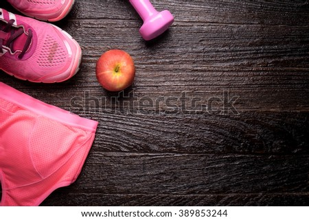 Pink Sneakers and dumbbells fitness on wooden desk top view. - stock photo
