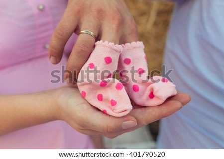 pink socks newborn baby on hands of parents mom and dad - stock photo