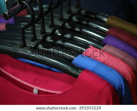 pink t shirt hang background , shop, looking through new clothes during shopping,Colorful women's dresses on wood hangers in a retail shop. Fashion and shopping business concept.