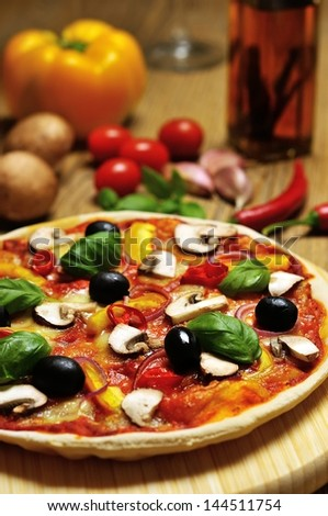 pizza on wooden board with some ingredients in the background - stock photo
