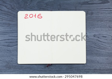 2016 planning agenda. Book on wood background. - stock photo
