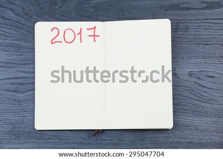2017 planning agenda. Book on wood background. - stock photo