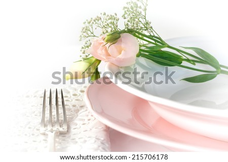 Plate and pastel flowers decoration on white background - stock photo