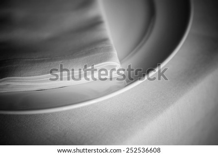 (plate, dish, tablecloth, napkin, fork) serving dinner table in BW in small DOF