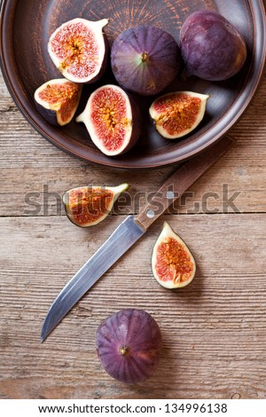 plate with fresh figs and old knife on rustic wooden table - stock photo