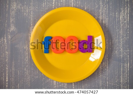 Plate with word FOOD on the wooden background.