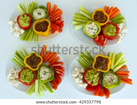4 plates of triple dips with 3 sauces: cashew chive sour cream, spicy tomato and avocado guacamole, served with cauliflower, red peppers, cucumbers, celery, and carrot sticks - raw vegan healthy food - stock photo