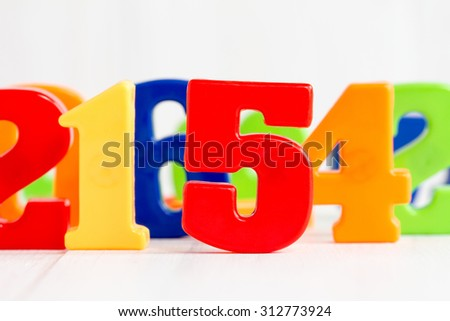 Playing with colored numbers over a white background - stock photo
