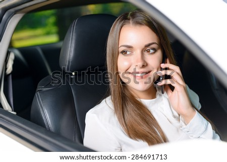 Pleasant conversation. Beautiful youthful woman sitting in car an talking per mobile phone.