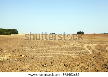 plowed land in the agricultural field after harvest of cereal, tractor tracks on the ground