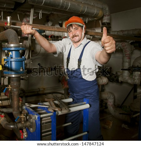 Plumber working with tubes and giving thumb up