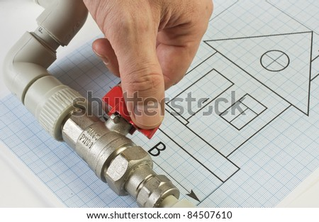 plumbing fittings in hand on the drawing - stock photo