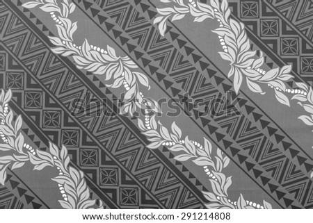 Polynesian cloth fragment with a white  leis on a black and gray Polynesian background. - stock photo