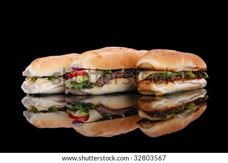 3 popular sandwiches - Chicken Caesar, Deli giant and Philly on black - stock photo
