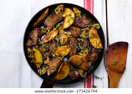 Pork ribs fried with potato on a frying pan. top view. style vintage. selective focus - stock photo