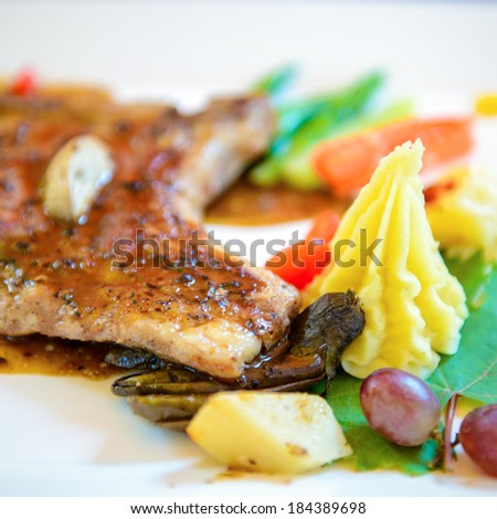 Pork steak with vegetables on white plate