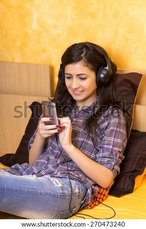 Portrait of a beautiful happy girl  with headphones and mobil phone lying on  bed in the bedroom - stock photo