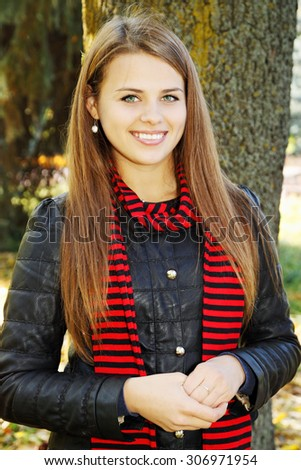 Portrait of a beautiful young woman sitting near a tree - stock photo