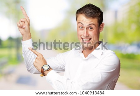 """Portrait Of A  Excited Young Man Pointing Up, Outdoor