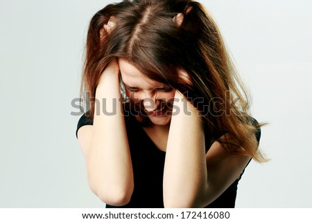 Portrait of a frustrated young screaming woman pulling her hair on gray background - stock photo