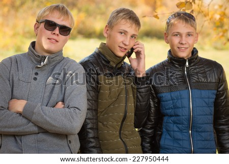 Portrait of a group of young men standing in autumn park, two of the boys twin brothers. Image with Instagram-like filter - stock photo