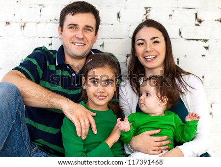 Portrait of a happy smiling family near white brick wall - stock photo