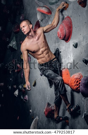 Portrait of a shirtless athletic male on climbing, indoor wall.