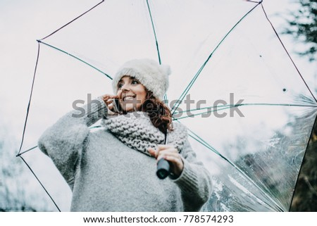 Portrait of a young and pretty woman in the middle of winter afternoon talking with her mobile phone in the beautiful countryside. Lifestyle.