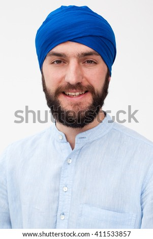 Portrait of a young bearded man in a turban smiling, white background