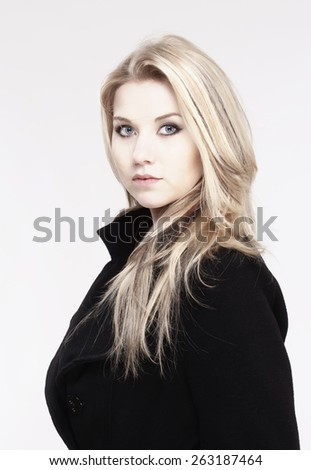Portrait of a Young Woman with Blond Hair and Black Coat - stock photo