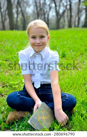 Portrait of adorable cute little girl with book sitting outside on grass - stock photo