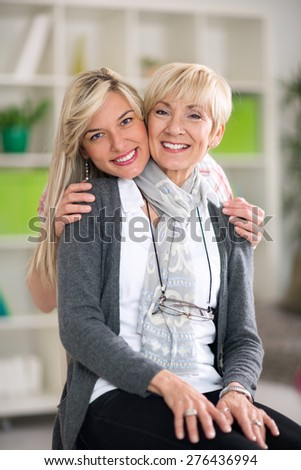 Portrait of adult mother and daughter hugging at home  - stock photo