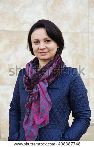 Portrait of an adult woman in a dark blue jacket and cravat. - stock photo