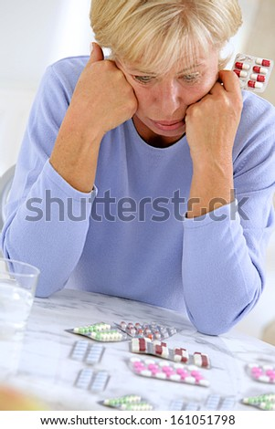 portrait of an senior woman stressed in front of  pills and tablets