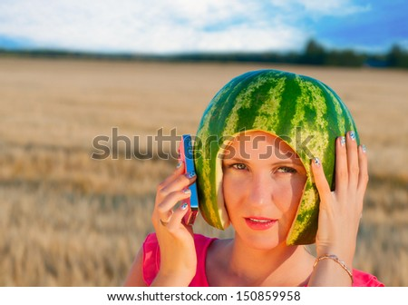 portrait of beautiful sexy young woman model with water-melon on head, woman speaking by phone - stock photo