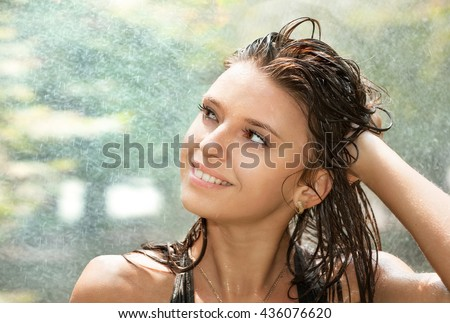 Portrait of beautiful young happy woman in spray of water  - stock photo