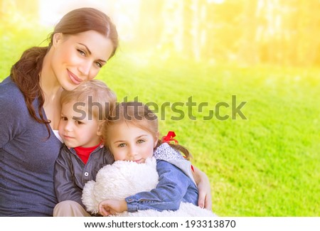Portrait of beautiful young mother with cute daughter and son sitting on the meadow, sunny day, love and happy family concept