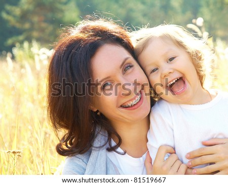 Portrait of  beautiful young woman hugging her little girl - stock photo