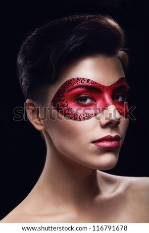 portrait of beutiful woman in red leather mask on dark background - stock photo