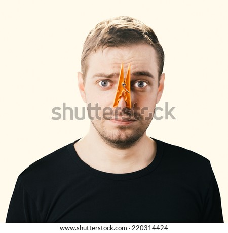 Portrait of caucasian man with orange clothespin on his nose - bad smell concept photography. Color toned image. - stock photo