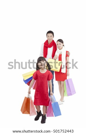 Portrait of daughter holding shopping bags,parents holding shopping behind