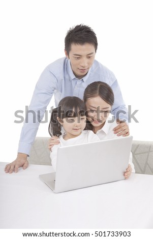 Portrait of daughter playing laptop  with parents